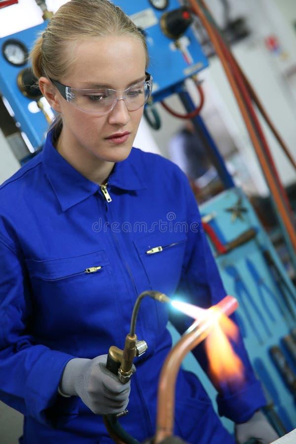 Vrouw studenty in loodgieterswerk beroepsopleiding stock afbeeldingen