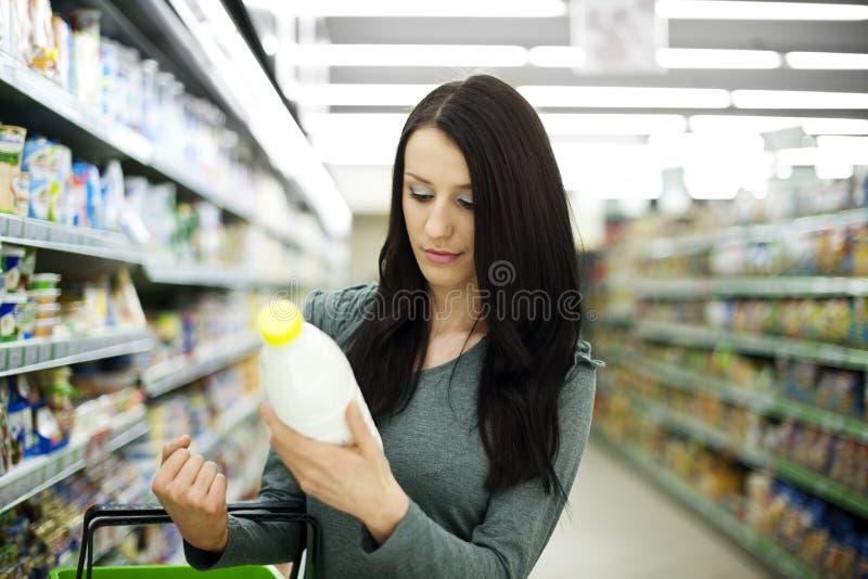 Vrouw in supermarkt stock afbeelding