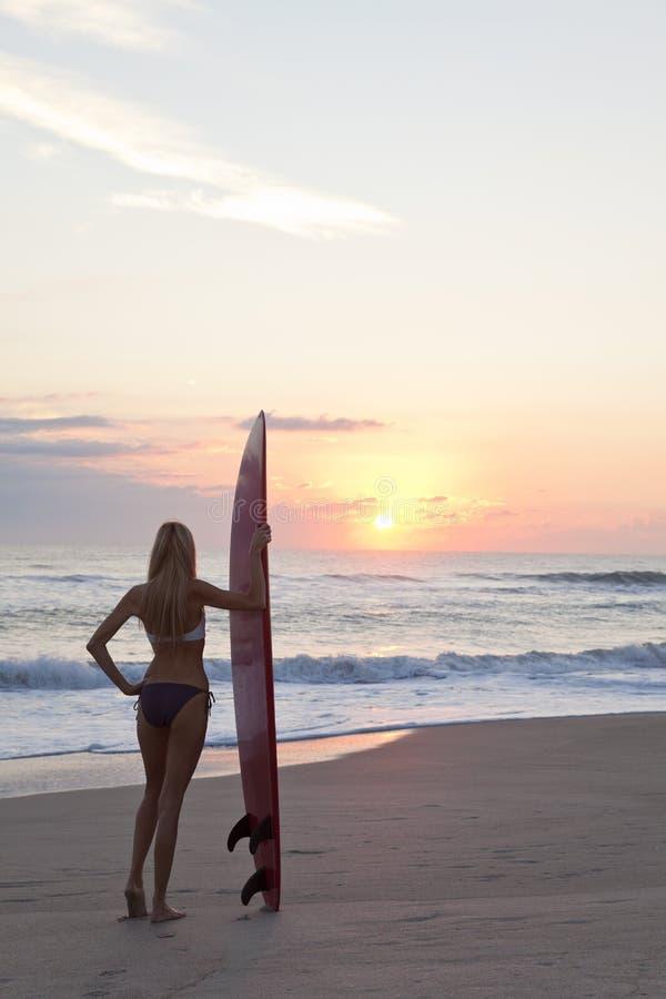 Vrouw Surfer in Bikini & Surfplank bij het Strand van de Zonsondergang stock afbeeldingen