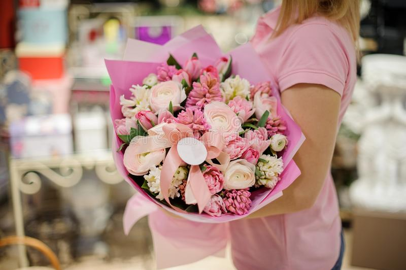 Vrouw tedere roze bloemsamenstelling houden die bestaand uit rozen, ranunculus en andere mooie bloemen royalty-vrije stock afbeeldingen