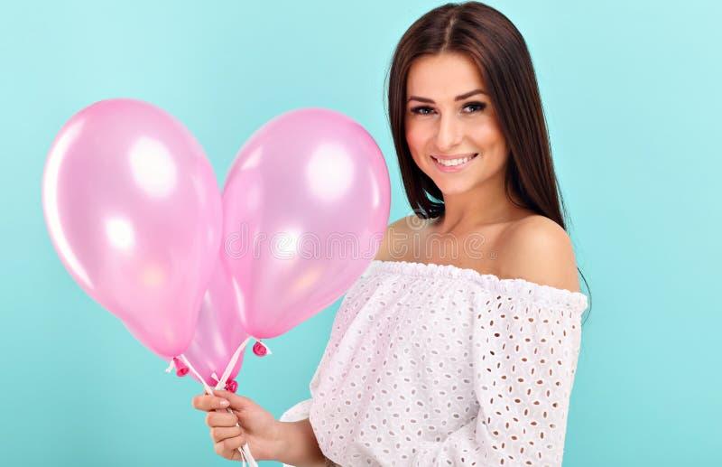 Vrouw tegen blauwe muurachtergrond met baloons stock fotografie