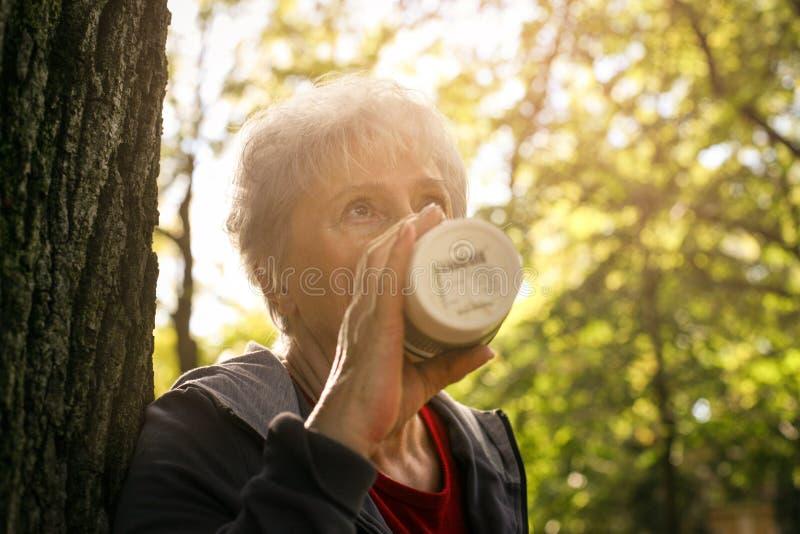 Vrouw in tegen de boom leunen en park die coffe drinken stock foto's