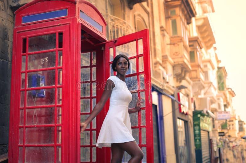 Vrouw in telefooncel stock afbeelding
