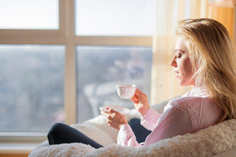 Vrouw thuis en het drinken thee die ontspannen royalty-vrije stock foto