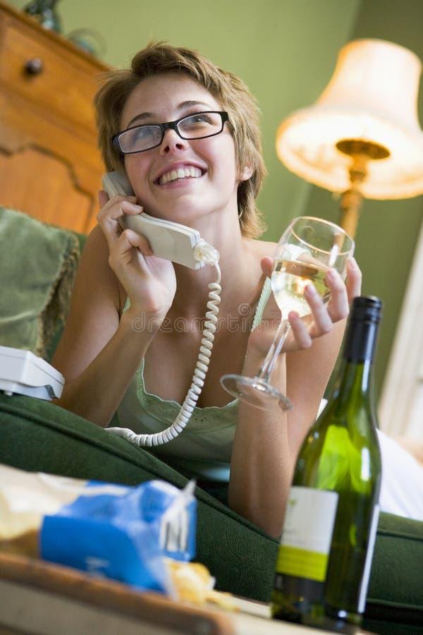 Vrouw thuis op telefoon stock afbeeldingen