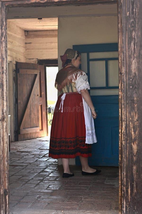 Vrouw in traditioneel kostuum in de gang van een historisch buitenhuis stock foto's