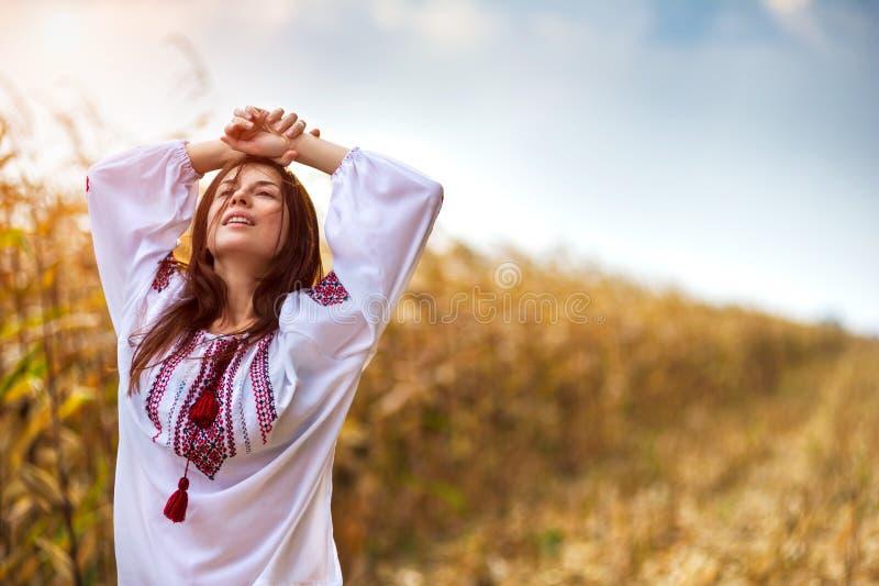 Vrouw in traditioneel overhemd die zich op cornfield bevinden royalty-vrije stock afbeelding