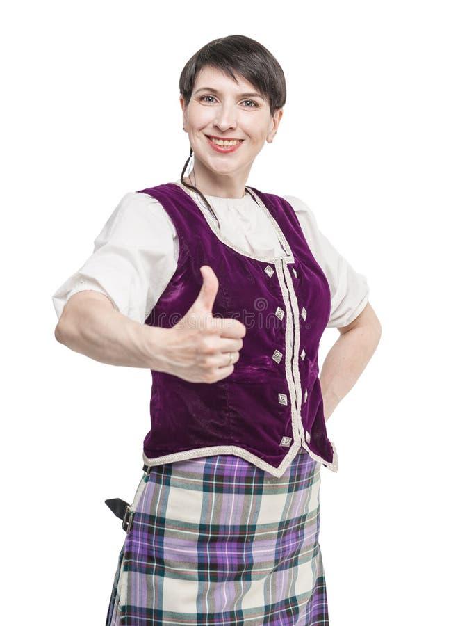 Vrouw in traditionele kleding voor Schotse dans die duimen tonen stock foto's
