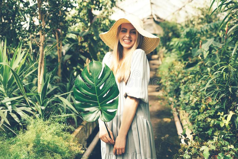 Vrouw in tropische oranjerie met monsterablad royalty-vrije stock afbeeldingen
