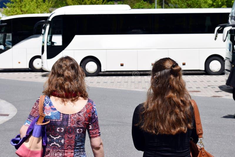 Vrouw twee die aan bus lopen royalty-vrije stock afbeeldingen