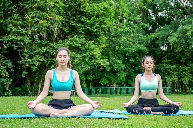 Vrouw twee die in een positie van de lotusbloemyoga inzake een yogamat mediteren in het park stock fotografie