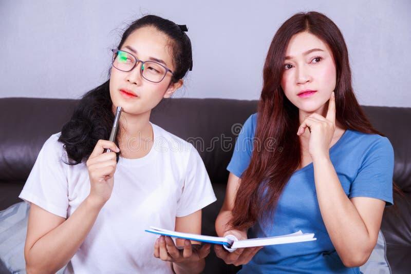 Vrouw twee die met een boek op bank in woonkamer thuis denken royalty-vrije stock foto's
