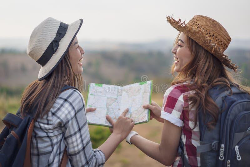 Vrouw twee die richting op plaatskaart zoeken terwijl het reizen stock afbeeldingen