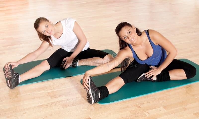 Vrouw twee die uitrekkende oefening doet bij gymnastiek stock fotografie