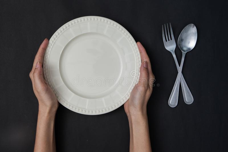 Vrouw twee handen houdt een lepel en een vork en witte schotel op zwarte bedelaars royalty-vrije stock afbeeldingen