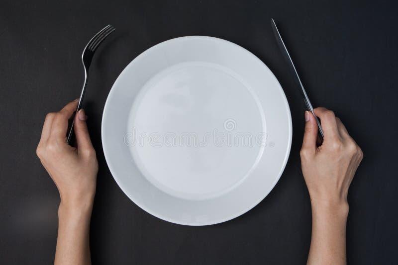 Vrouw twee handen houdt een mes en een vork en witte schotel op zwarte bedelaars stock afbeelding