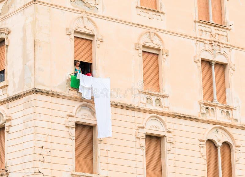 Vrouw uit het venster van haar oud flatgebouw die haar te drogen wasserij hangen stock foto