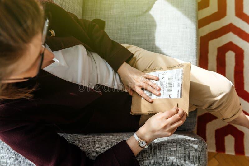 Vrouw unboxing uitpakkend Amazonië Com-doos stock foto's