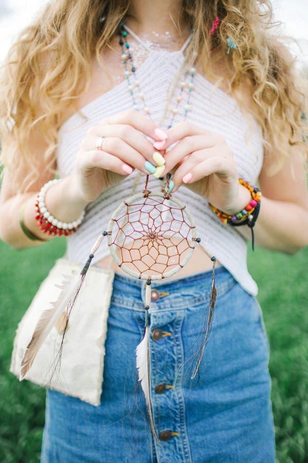 Vrouw van de blonde de krullende hippie met droomvanger in handen royalty-vrije stock foto