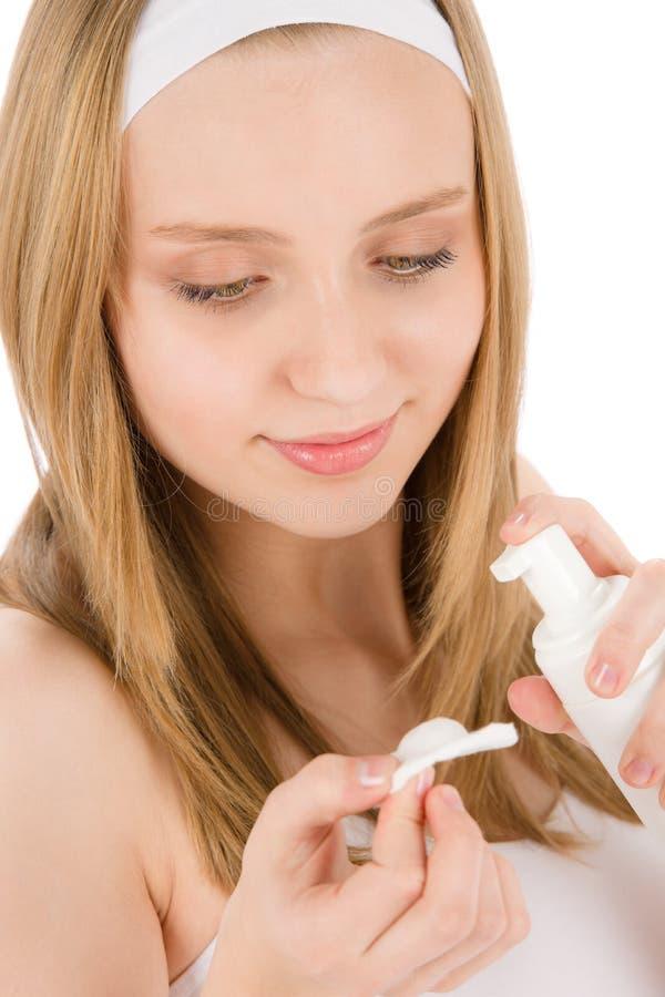 Vrouw van de de zorgtiener van de acne past de gezichtsroom toe stock foto's