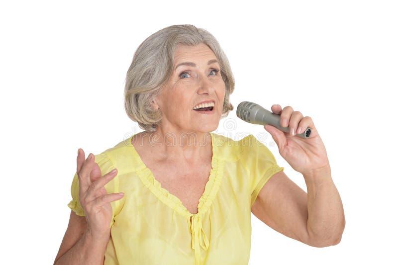 Vrouw van de portret de hogere die zanger op witte achtergrond wordt geïsoleerd stock afbeelding