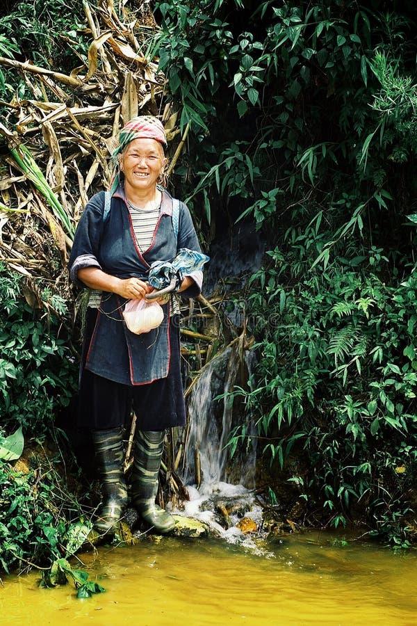 vrouw van de zwarte hmongstam die zich naast een gele gekleurde stroom en een kleine waterval bevinden stock foto's