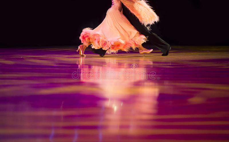 Vrouw van een oranje jer en een mantel met zwarte kleerkleed Latino dansen stock foto's