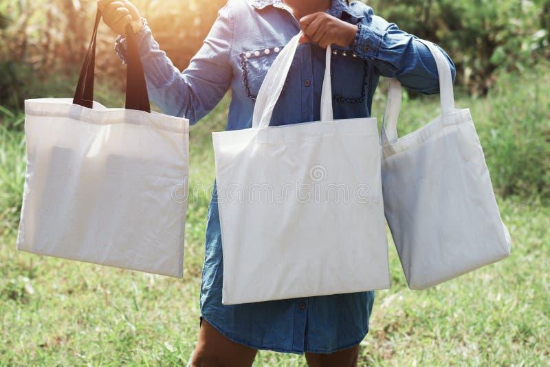 vrouw van het katoen Tote Bag drie van de handholding op groen gras backg stock foto's
