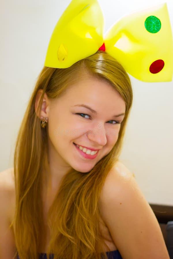 Vrouw van 20 jaar in de gele boog van kinderen stock afbeeldingen