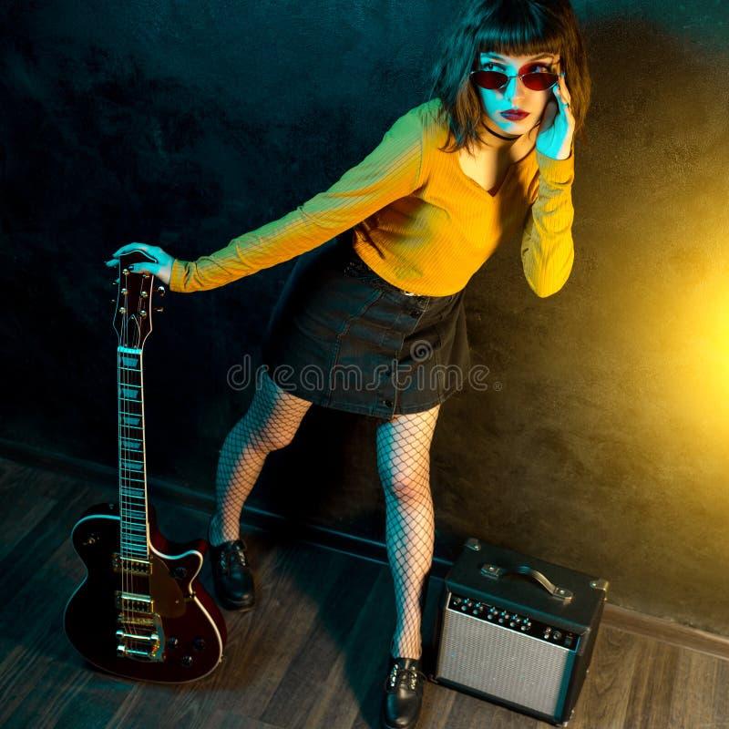 Vrouw van manier de jonge hipster met krullend haar met rode gitaar in neonlichten De musicus van de rots speelt elektrogitaar royalty-vrije stock foto