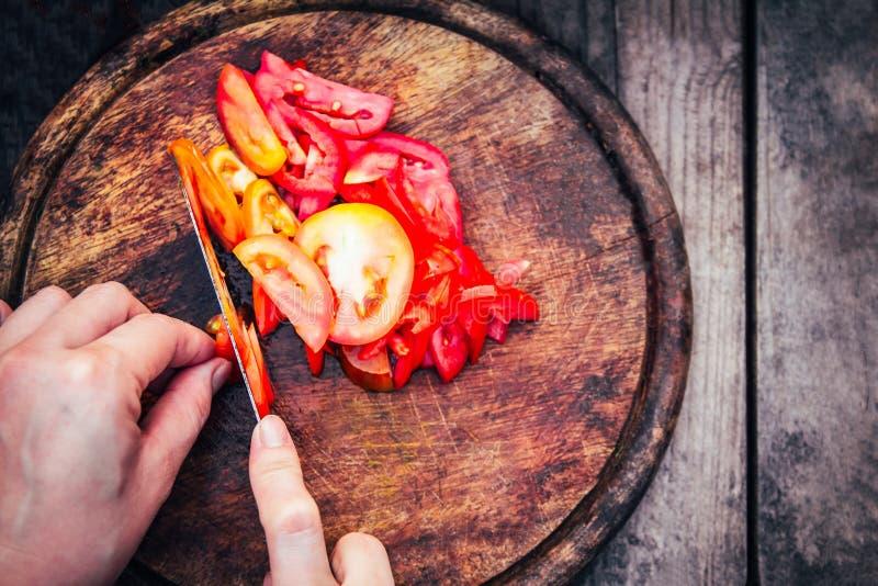 Vrouw van rode tomaten van de Hand de scherpe versheid op houten om de maaltijd voor te bereiden royalty-vrije stock afbeeldingen