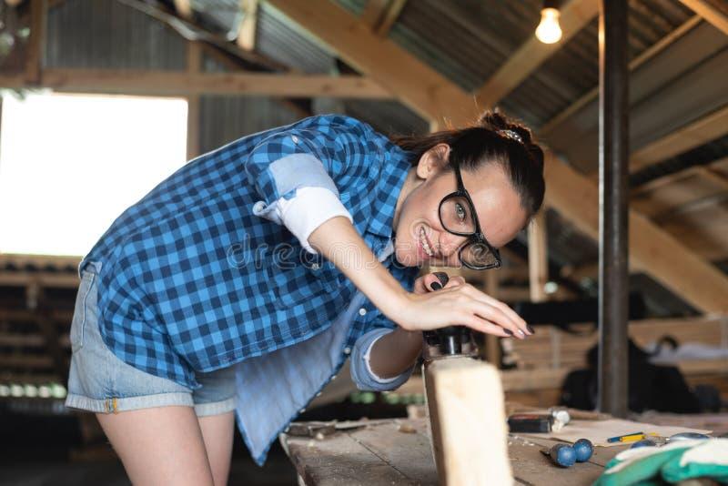 Vrouw in veiligheidsbril die planer werken aan houten Raads vooraanzicht stock afbeelding