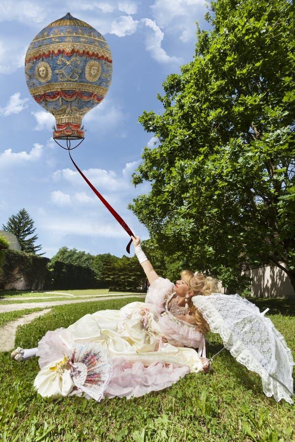 Vrouw in Venetiaans kostuum die op het groene park liggen die een oude ballon houden royalty-vrije stock fotografie