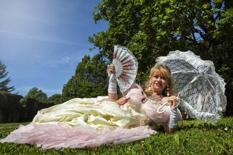 Vrouw in Venetiaans kostuum die op het groene park met witte paraplu liggen stock fotografie