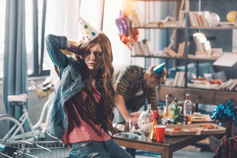 Vrouw in verjaardagshoed, man het schoonmaken erachter in slordige ruimte na partij royalty-vrije stock foto's