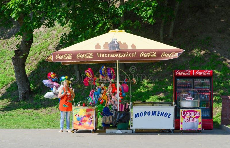 Vrouw-verkoper in park bij teller met roomijs, ballons stock foto's