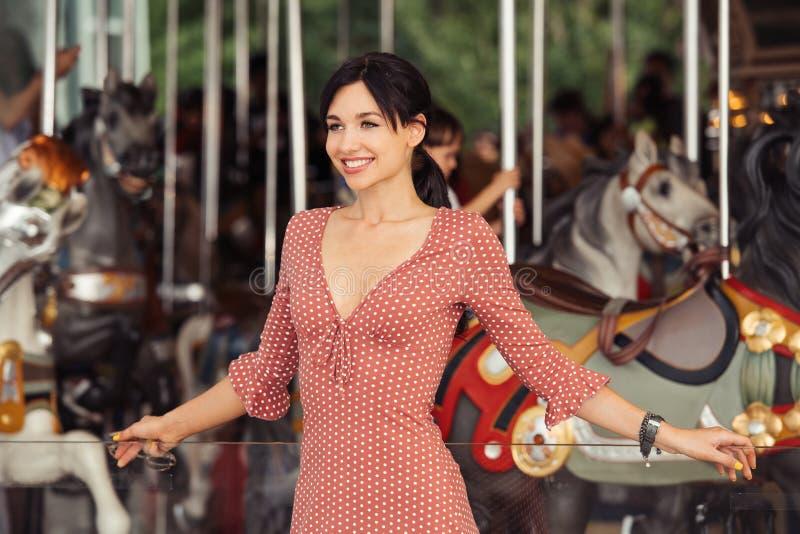 Vrouw in vermaak en gelukkig wachten voor de rit bij carrousel wordt opgewekt die royalty-vrije stock foto