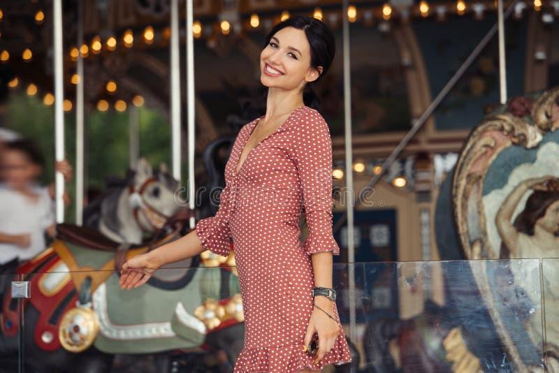 Vrouw in vermaak en gelukkig wachten voor de rit bij carrousel wordt opgewekt die stock foto's