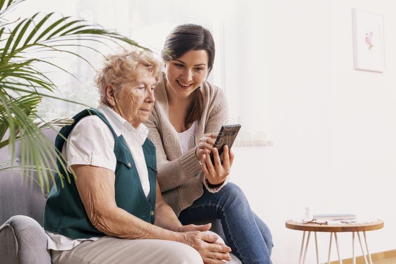 Vrouw in verpleeghuis met haar kleindochter die haar toont hoe te om een mobiele telefoon te gebruiken stock afbeeldingen