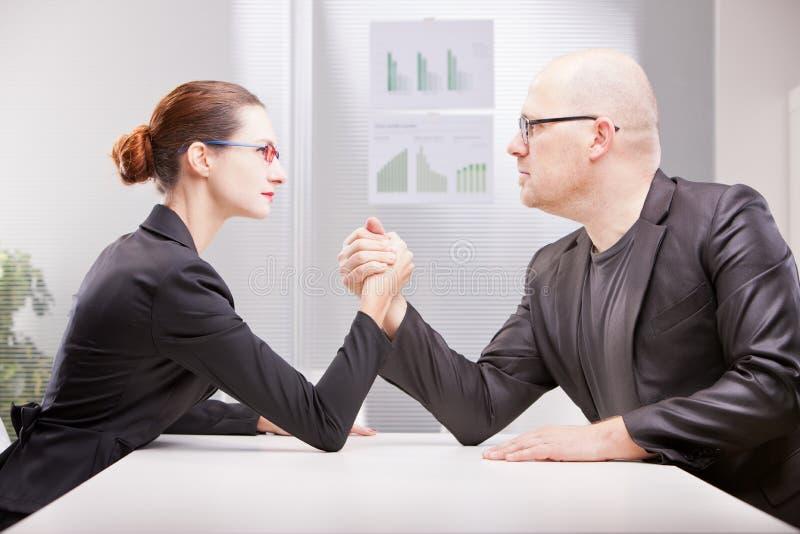 Vrouw versus man het bedrijfswapen worstelen stock fotografie
