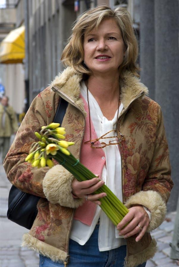 Vrouw vijftig op de straat met bloemen stock afbeelding