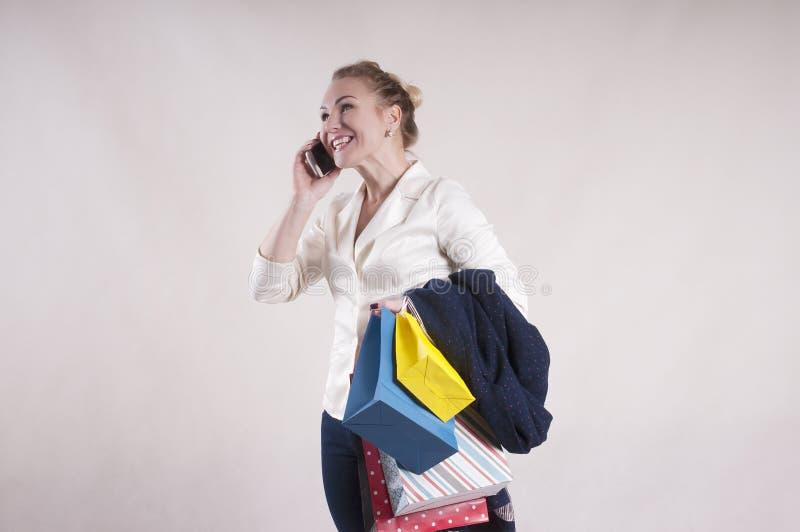 Vrouw volwassen het winkelen zakstudio met telefoon royalty-vrije stock foto