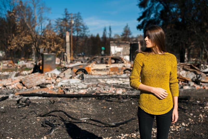 Vrouw voor haar gebrand huis na brandramp stock fotografie