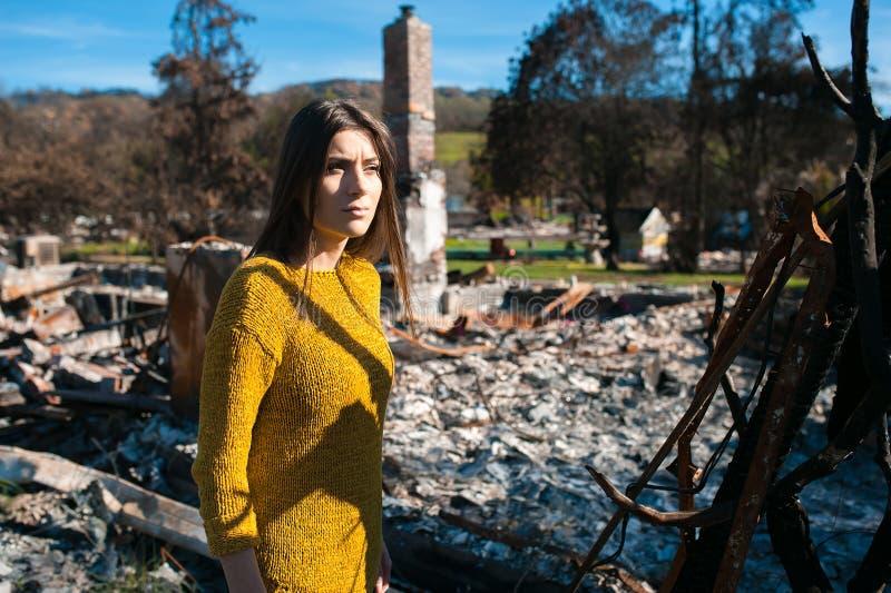 Vrouw voor haar gebrand huis na brandramp royalty-vrije stock afbeelding