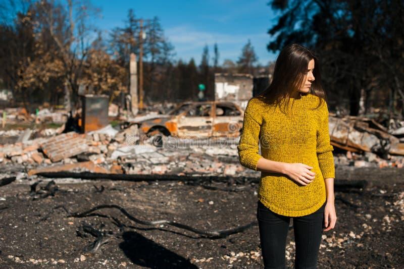 Vrouw voor haar gebrand huis na brandramp stock foto's