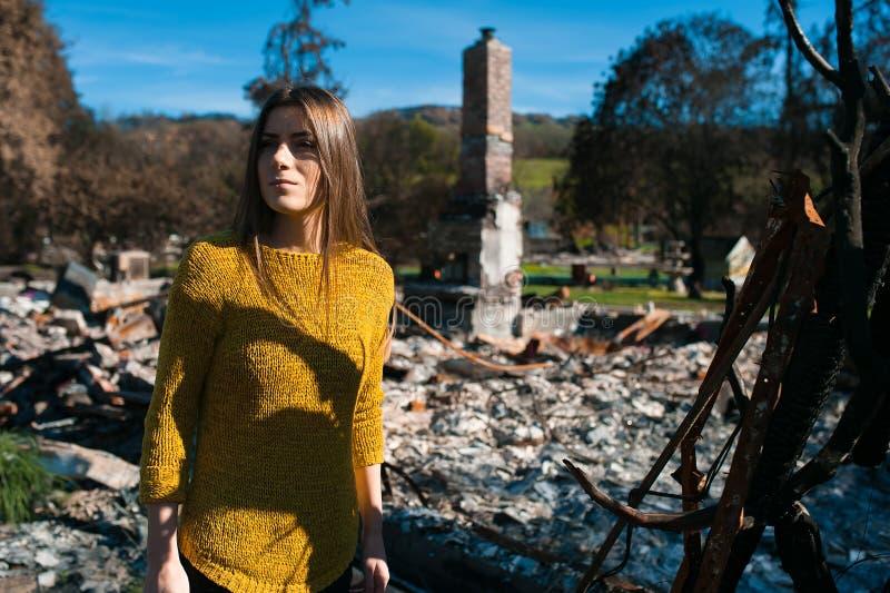 Vrouw voor haar gebrand huis na brandramp royalty-vrije stock fotografie