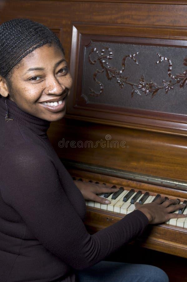 Vrouw voor oude piano stock afbeelding