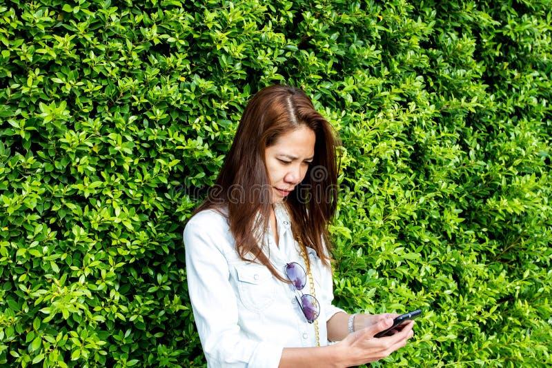 Vrouw vrouwelijke het gebruiken smartphone van iphonecellphone tegen de rug stock fotografie