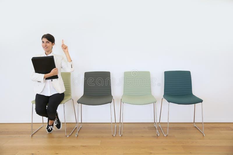 Vrouw in wachtkamer poiting vinger omhoog, idee stock afbeeldingen