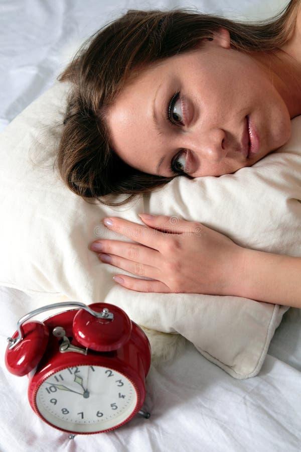Vrouw wakker met wekker royalty-vrije stock afbeelding